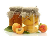 Canned apricots in a jars and sweet apricots isolated on white — Stock Photo