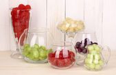Color candies in glasses on wooden background — Stock Photo