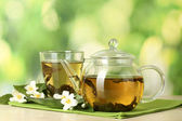 Green tea with jasmine in cup and teapot on wooden table on green background — Photo