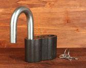 Vecchio lucchetto con chiavi sul primo piano sfondo in legno — Foto Stock