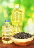 Sunflower oil in bottles with sunflower seeds on green background close-up — Stock Photo
