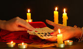Fortune-telling and woman's hands on black backcground — Stock Photo