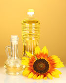 Sunflower oil in a plastic bottle and small decanter on yellow background — Stock Photo