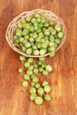 Green gooseberry in basket on wooden background — Stock Photo