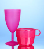 Bright plastic tableware on blue background — Stock Photo