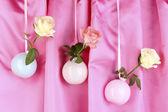 Hermosas rosas en floreros colgantes sobre fondo de tela — Foto de Stock