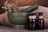Thyme herb and mortar on wooden table on brown background — Stock Photo