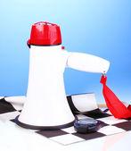 Bandiera a scacchi finitura e megafono su sfondo blu — Foto Stock