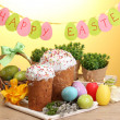 Beautiful Easter cakes, colorful eggs in basket and candles on wooden table on yellow background — Stock Photo