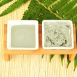 Cosmetic clay for spa treatments on straw background close-up — Stock Photo