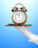 Hand i handske håller silverbricka med väckarklocka på blå bakgrund — Stockfoto
