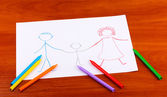 Children's drawing of family and pencils on wooden background — Stock Photo
