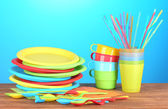 Bright plastic disposable tableware on wooden table on colorful background — Stock Photo