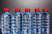 Plastic bottles of water on grey background — Stock Photo