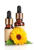 Medicine bottles and beautiful calendula flowers, isolated on white — Stock Photo
