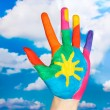 Brightly colored hand on sky background close-up — Stock Photo