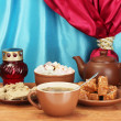 图库照片: Teapot with cup and saucers with oriental sweets - sherbet, halva and turkish delight on wooden table on a background of curtain close-up