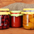Jars with canned fruit on wooden background close-up - Stockfoto