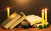 Old books, scrolls, ink pen inkwell and candles on wooden table on brown background — Stock Photo