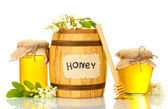 Sweet honey in barrel and jars with acacia flowers isolated on white — Stock Photo