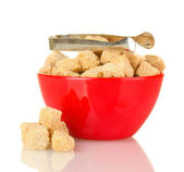 Brown cane sugar cubes in bowl with sugar-tongs isolated on white — Stock Photo