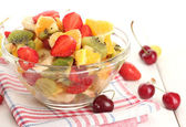 Glass bowl with fresh fruits salad and berries on white wooden table — Stock Photo
