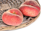 Ripe fig peaches on wicker mat isolated on white — Stock Photo