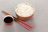 Bowl of rice and chopsticks on grey mat — Stock Photo
