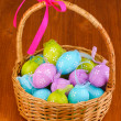 colorful easter eggs in basket on wooden background — Stock Photo #11920265