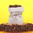 Coffee beans in canvas sack on yellow background — Stock Photo