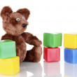 Sitting bear toy and color cubes isolated on white — Stock Photo #11920628