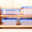 Plastic containers for food on shelf on wooden background — Stock Photo
