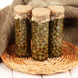 Stock Photo: Glass jars with tinned capers in sack on white wooden background