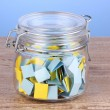 Stock Photo: Pieces of paper for lottery in jar on wooden table on blue background
