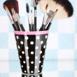 Makeup brushes in a black polka-dot cup on colorful background — Photo