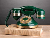 Retro phone standing on book on wooden table on grey background — Stock Photo