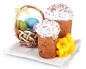 Beautiful Easter cakes, colorful eggs in basket and flowers isolated on white — Stock Photo
