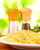 Composition of the delicious spaghetti on green background close-up — Stock Photo