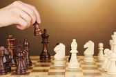 Chess board with chess pieces on brown background — Stock Photo