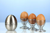 Egg timer and egg in metal stand on blue background — Stock Photo