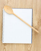 Open cookbook and kitchenware on wooden background — Stock Photo