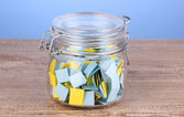 Pieces of paper for lottery in jar on wooden table on blue background — Stock Photo