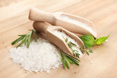 Salt in shovels with fresh basil, rosemary and thyme on wooden background — Stock Photo