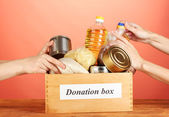 Donation box with food on red background close-up — Stock Photo