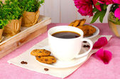 Cup of coffee, cookies and flowers on table in cafe — Stock Photo