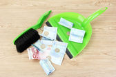 Broom sweep the euro on white background close-up — Stock Photo