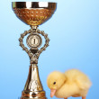 Duckling and champion cup on wooden table on blue background — Stock Photo