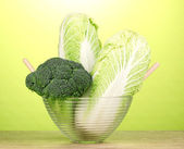 Glass bowl with cabbages and broccoli on wooden table on green background — Stock Photo