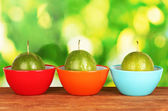 Three green passion fruit in bowls on green background — Stock Photo