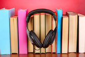 Headphones on books on wooden table on pink background — Stock Photo